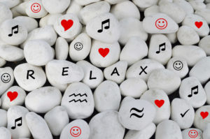 Relax written on white stones and other relaxation symbols