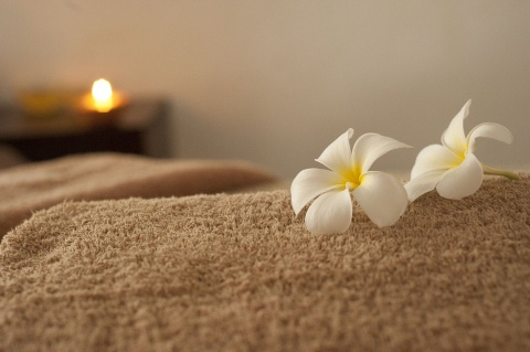 a spa therapy room with a flower and towel on the bed