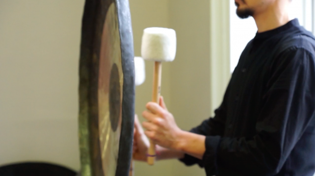 a man playing the gong in a sound therapy treatment