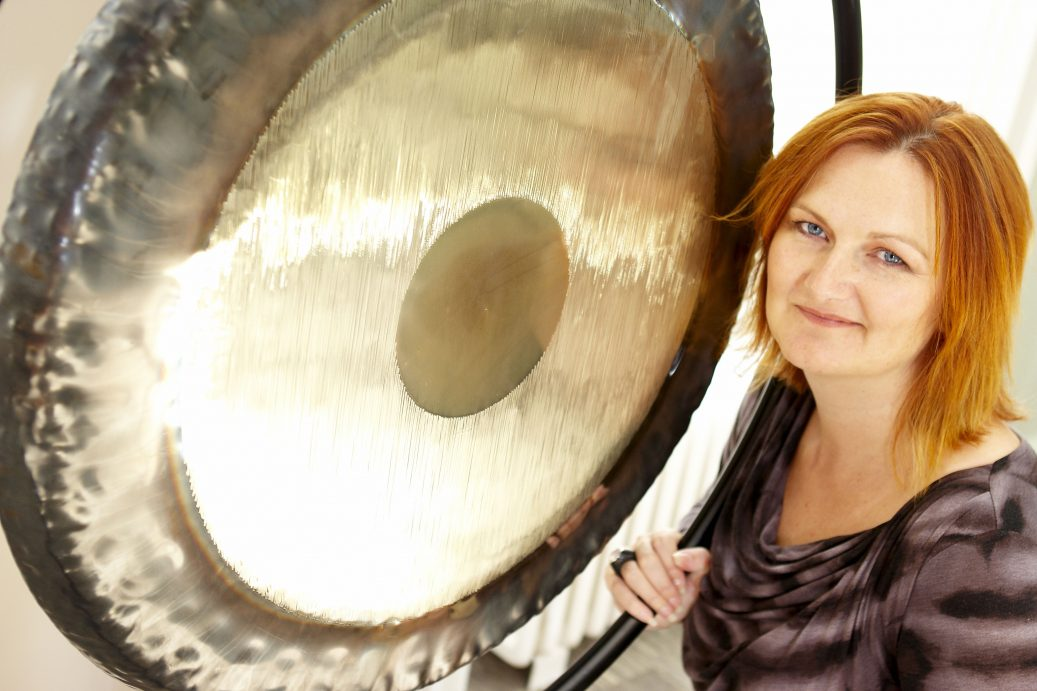 Lyz cooper british academy of sound therapy next to a gong